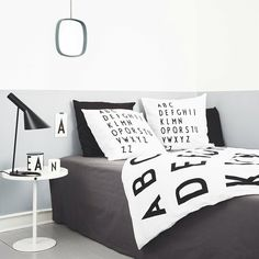 Graphic bedroom! Typography: Arne Jacobsen. Black and white bed linen in soft cotton and porcelain in fine bone china. Table to Go and Television mirror designed by Design Letters.