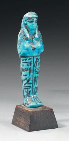 Oushebti inscrit sur deux colonnes ventrales au nom de Hor-Khebi, père divin, chef des scribes du temple d'Amon. Il porte la perruque tripartite striée ceinte d'un bandeau et les instruments aratoires… - Thierry de Maigret - 11/12/2015