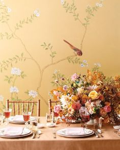 "When delicate pinks blend with fiery shades of copper, your decor takes on luxurious depth. To create tables that seem plucked from a romantic painting, we supplemented the copper and rose tones with a lush centerpiece of roses, dahlias, mums, scabiosa, bittersweet, pieris seed heads, beech foliage, and gilded leaves. ""Golden Garden"" buffet plate, and dinner plate, both Villeroy & Boch. ""Badminton"" wallpaper, de Gournay."