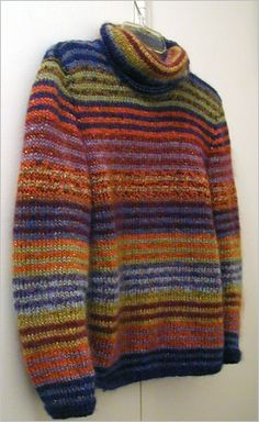 Summary: Long, oversized multi-color striped, long-sleeved turtleneck pullover.