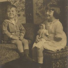 The little boy is holding what appears to be an early Model T Ford toy car.  His sister is sporting cute little round spectacles and is holding a rag doll.