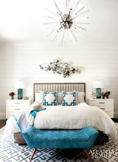 To give the master bedroom a softer touch, Watford introduced more feminine accents, such as the Jonathan Adler sculpture resting above the headboard and a statement Arteriors chandelier. Bed, Plantation LA. Bedside tables, West Elm. Lamps, Regina Andrews.