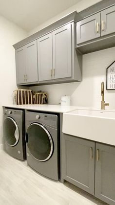 Home Decor Discover Laundry room with gray cabinets & gold hardware Beautiful utility room with gray painted cabinets gold hardware apron sink and light wood floors.  Click to see more model home design ideas... THE DECORATING COACH Mudroom Laundry Room, Laundry Room Layouts, Laundry Room Remodel, Laundry Room Organization, Laundry Room With Sink, Laundry Room Sink Cabinet, Organization Ideas, Laundry Room Floors, Organized Laundry Rooms