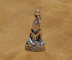 Fair Trade hanger uit Thailand gemaakt van sterling zilver (925) met een beeldje van Boeddha. Dit hangertje is driedimensionaal. Deze Boeddha vond verlichting onder de heilige bodhiboom, nadat hij een rijk leven achter zich liet en vele ontberingen in het leven leerde kennen. Hij is de oprichter van het Boeddhisme en heeft vele leerlingen zijn wijze lessen (dharma) doorgegeven.