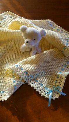 Copertina baby bimbo, in lana lavorata ai ferri, punto fantasia con bordo all'uncinetto e nastro di raso azzurro. Mis 80x70