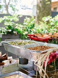 How To Host a Backyard Barbecue Wedding Shower: When it comes to hot food, disposable catering trays warmed with ethanol gel cans are the best fit. Disguise the low-budget trays by placing them toward the back of the buffet table, then layering other platters and stands in front of and around them. From DIYnetwork.com