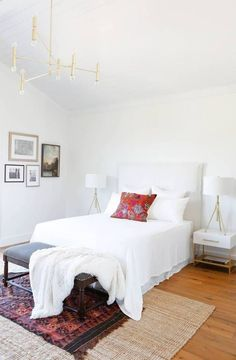 Bright and airy bedroom with a gold chandelier, layered rugs, and matching table lamps