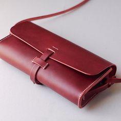 くも舎の耳つきカバンは、最上級のオイルドレザーを使用した横長の小さなバッグです。サイズは一般的な長財布や文庫本、携帯電話などが入る大きさです。カバンの側面には大きな耳がついていますので、長いベルトをつければショルダーバッグに、短いベルトをつければハンドバッグにもなります。また、別売りの自転車ベルトを使うと、サドルバッグにもなります。