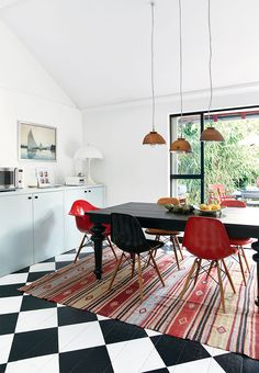 robin egg kitchen cabinets, ornamental rug and eames chairs around the dining table