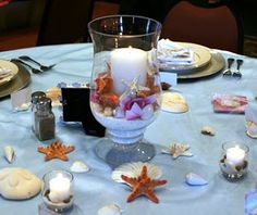 Hurricane candle holder, shells, starfish, silk flowers...white table cloth with a blue mist organza overlay to give the feel of the ocean...mini glass votives to surround it with sand and shells