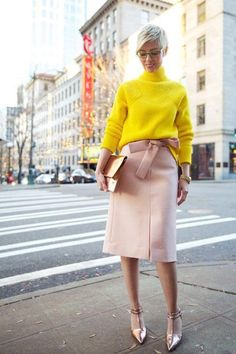 A woman is wearing a yellow sweatshirt and rose skirt and shoes