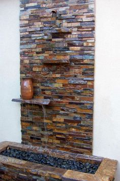modern water features built in wall stone with floating shelf
