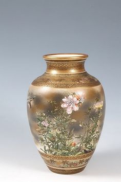 A 19TH CENTURY SATSUMA PORCELAIN VASE, of baluster form, with multiple diaper, floral, and Greek key borders enclosing two large vignettes, one with figures in a forest landscape with pagodas, the other with a bird in flight amongst floral foliage.