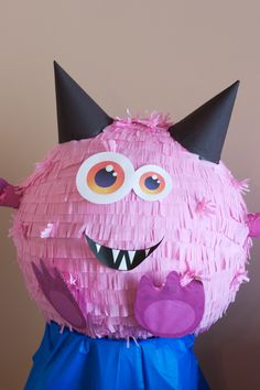 Homemade Monster Piñata. Use a thick balloon for the shape and cover with newspaper and flour paste. Make ears with party hats, arms with toilet paper rolls, and legs with miniature slinkees. Paint and cover with crepe paper fringed with scissors. Insert candy through the arm holes.