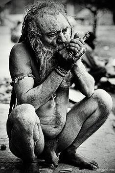 A Naga Sadhu (wandering Hindu holy man) smoking Chillum during the Kumbh Mela. These Sadhus remain naked all the time, have long dreadlocks, and smear their bodies with ash. Kumbha (pot) Mela (fair…