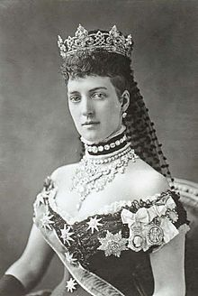 Alexandra of Denmark, the Queen Consort of Edward VII.  She nearly always wore a 'dog collar' choker necklace or a necklace on a band of velvet, as in this photo, to hide a scar on her neck.