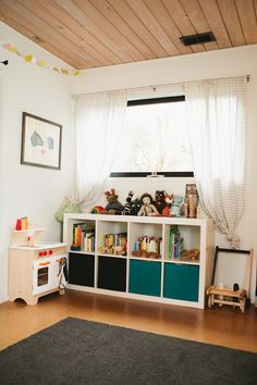 Two-high IKEA EXPEDIT with turquoise canvas bins - kid height and clean looking