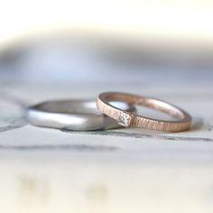 プラチナとピンクゴールドでおつくりした結婚指輪(オーダーメイド/手作り) アンティークな雰囲気がお好みのお二人。 コレクションを試着しながら、それぞれのデザインを決めていきました。   男性は柔らかなゆらぎのあるフォルムが気に入り、厚みと質感にこだわって プラチナのつや消しのホーニング仕上げでお仕立て。 女性はピオージャのデザインが気に入り、一番指にあうピンクゴールドで。 リングの側面を、男性とお揃いのつや消しホーニング仕上げでお作りしました。 [マリッジリング,marriage,weding,ring,bridal,diamond,gold,Pt900,ith]