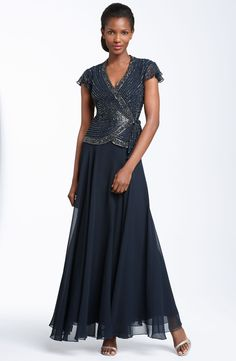Irridescent beading highlights the faux-wrap front bodice of an elegant chiffon gown with the look of two pieces and the ease of one. Fluttery cap sleeves balance the flowing skirt.
