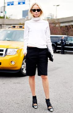 A white turtleneck is worn with knee-length shorts, Ray-Ban sunglasses, and metal-toe ankle booties