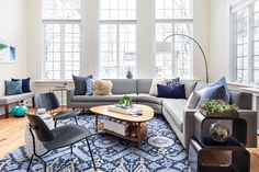 """The family room needed the most work. According to Sara, """"The family room was the most transformative space in the home. It was originally used as a shallow fountain, with a sunken tile floor. Several loads of concrete were required to level the floor for the installation of hardwood floors."""" Now, it makes for a sun-washed solarium meets living room."""