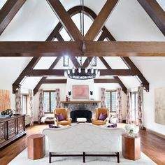 Designer Claire Paquin's plan for this great room was client-driven — a center chandelier is inspired by a fixture at the Biltmore Hotel the homeowners remembered seeing at their wedding ceremony. The chandelier perfectly fits the architecture of the home, harmonizing with the large wood beams and high ceilings for a dramatic look.