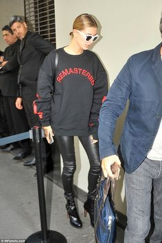 Comfy chic: Earlier on in the day, Hailey had worn the same racy jeans and boots to D&G's MFW SS17 show - though she'd traded the coat and crop for a black slogan sweater