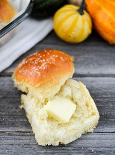 Overhead view of one homemade dinner roll sliced in half with a square of butter melting on it