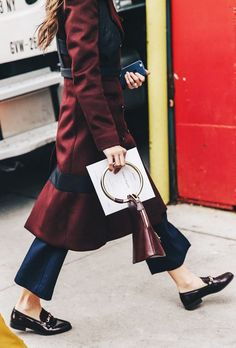 A burgundy coat is paired with a burgundy bag, navy trousers, and black loafers