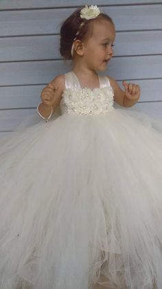 Make your wedding stand out with this beautiful Ivory Flower Girl Dress. This multilayer dress is made with yards and yards of premium soft tulle. Embellished with two rows of ivory flowers featuring rhinestone encased faux pearls. The double ivory satin straps lay over the shoulders