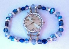 Large round pearl watch face is surrounded by rhinestones.  Band features variety of blue iridescent beads with clear crystal rondelles.