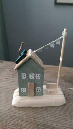 This is the sweetest little duck egg blue driftwood and reclaimed wooden cottage. A tiny wooden blue heart is anchored to the driftwood roof by a rusty nail, and pale blue bunting is tethered to a flagpole. A tall driftwood door sits at the front and is joined by the tiniest wooden