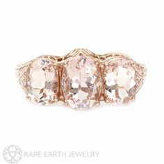 Elaborate filigree vines, leaves and flowers adorn this exceptional Art Nouveau inspired three stone ring. Beautiful faceted ovals of natural Morganite $1015