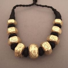 22ct gold Afghan necklace on pitch (resin) made up of 9 beads with geometrical forms and engravings and dating from first half of the 20th century
