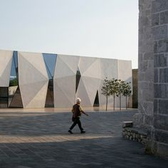 Faceted concrete blocks protrude from one side of this sports hall in Croatia.