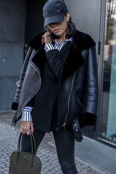 storm wears nina ricci bag and zara leather jacket in black with nike cap and andotherstories blouse theadorabletwo