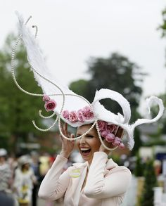 Anika Svenska laughs a she holds onto her hat as she poses for the media on the first day of the Royal Ascot horse race meeting in Ascot, England, Tuesday, June 18, 2013. (AP Photo/Alastair Grant)