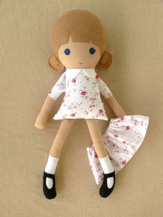 This is a handmade cloth doll measuring 18 inches. She is wearing a sweet, old fashioned white, pink, and red floral print dress with a matching removable skirt. Her light brown hair is worn in low, round ponytails. She has blue eyes, and a hand-embroidered face. She is made from 100% cotton fabrics, wool blend felt, and polyfill. Her seams are triple stitched, and she is firmly stuffed with fiberfill. Please handwash only. Thank you for viewing. See more at rovingovine.etsy.com.