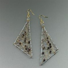 These elegant drop earrings are handcrafted in a chic, elongated triangular shape with a #wire-wrapped interior for remarkable texture. #Garnet gemstone beads, set on Nu Gold wire inside of the #aluminum rims, add eye-catching color to complete this spectacular look.These super light-weight #earrings are guaranteed to turn heads. $95