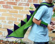 WE ARE NO LONGER TAKING ORDERS FOR CHRISTMAS DELIVERY. If you have a dinosaur crazy kid in your life, make their prehistoric dreams come true with this roarsome awesome cape! Whether for pretend play or a costume party, this cape will be the perfect finishing touch. Are they more of a dragon fan? No problem - order this in a red and green colourway and its just as effective for a tiny fire breather! Made from 100% cotton in your choice of colours, it has soft felt spikes, and a velcro nec...