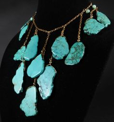 Spanish Queen Turquoise Bib Necklace  These polished slabs of natural Turquoise dangle from polished gold-tone chain in this extravagant bib-necklace. Make a bold and beautiful statement with this beautiful necklace.