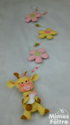 Pingentes de cortina com flores em feltro decoradas com detalhes em tecido.  Montados em cordão encerado, com aplicação de peças em acrílico e contas coloridas. Na ponta, um animal da selva muito fofo para dar um toque especial à peça. R$ 75,00