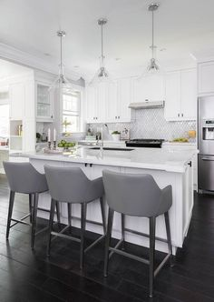 Gray and white kitchen features three glass cone shaped light pendants hung over a white island topped with a white marble countertop.