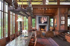 Tall, unadorned windows brighten the heavily-paneled dining room. While the dining table may be narrow, the piece makes up for it with its generous length. A heavy chandelier tops off the rustic look. Chandelier Design, Rustic Chandelier, Huge Windows, Floor To Ceiling Windows, Wood Panel Walls, Wood Paneling, Paneled Walls, Craftsman Fireplace, Arch Interior