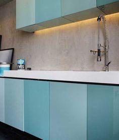 Com diversos armários, esta cozinha combinou tons de verde em degradê com a iluminação embutida e a parede que imita cimento queimado.