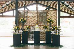 Mesa do bolo em preto, branco e amarelo (com bambu ao fundo) em casamento diurno. Foto: TudoViraFoto.