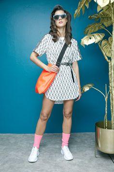 Vestido estampado Adidas, sneakers blancos GBG, crossbody naranja grande That´s It y lentes azul con rosa Karen Walker.