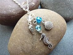 Seahorse and seashell necklace with blue and white crystals. This pretty beach and sea theme pendant necklace has a seahorse charm and 2