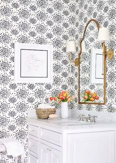 Black and white powder room is clad in white and black wallpaper, Hinson & Co Fireworks Wallpaper, lined with a gold mirror illuminated by brass and glass wall sconces, Camille Long Sconces, placed over a white cabinet vanity adorned with glass knobs topped with white marble fitted with a round sink and polished nickel cross handle faucet kit.
