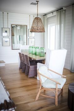 Beach cottage dining room with stacked hanging photos in gray gallery frames flanking large rectangular mirror on white paneled walls accented with gray sheer curtains over light wood floors.